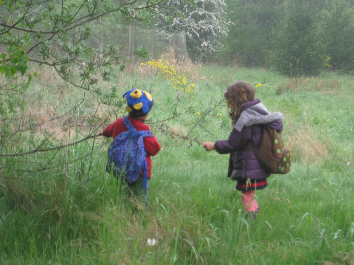 The day was wet with spring rain ... yet these two  kids were enthralled by the willow catkins. Enchanting! - photo by Jane